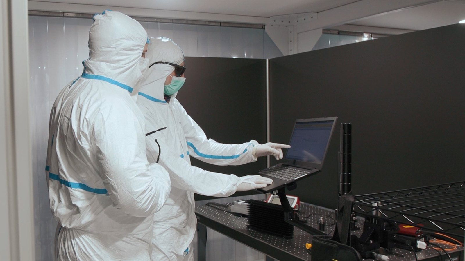 engineers on laptop in cleanroom: UnikLasers