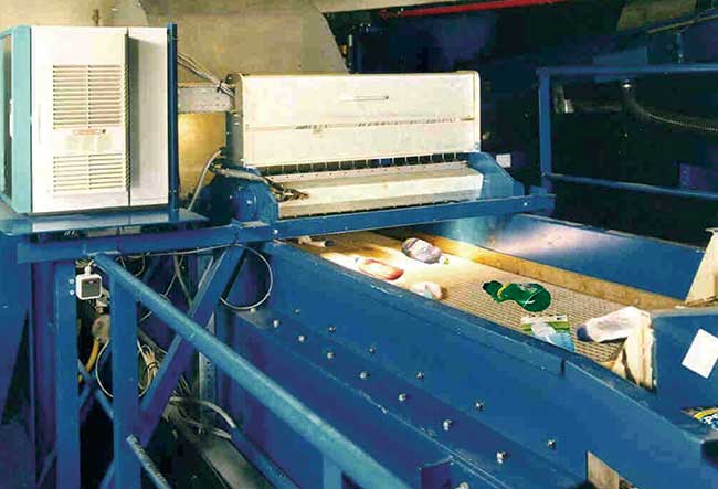 A sorting machine for plastic bottles samples spectra from multiple fiber optic ports across the conveyor belt to sort plastic bottles by type.