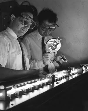 A laser in operation at the Electronics Resource Centers Space Optics Laboratory is checked by Lowell Rosen (left) and Dr. Norman Knable.