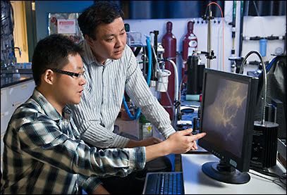 Graduate student Guosong Hong, left, and chemistry professor Hongjie Dai look at the vascular structures in a mouse model of peripheral arterial disease; blood vessels are shown in great detail using their new imaging technique called near-infrared II fluorescence imaging.