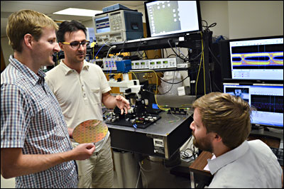 Members of the research team — from left, Jeff Shainline, Milos Popovic and Mark Wade — discuss the photonic-electronic microchip they developed.
