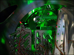 The inside of the experimental chamber showing the spectrometer (front) and the detector (black rectangle in the back) used for the detection of the x-ray emission spectra, and the glass fiber used for illumination of the sample (green).