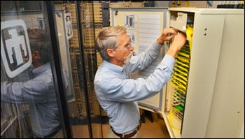 Steve Gossage, a senior engineer at Sandia National Laboratories, looks at fiber optics in a cable box that replaced heavier and bulkier copper cable for high-speed communication throughout much of the labs.