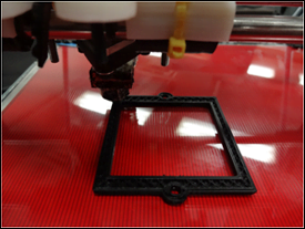An open-source self-replicating rapid prototyper printing a 3-D optical component — a filter bracket.