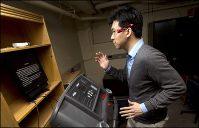 Purdue industrial engineering doctoral candidate Bum chul Kwon demonstrates a new system that allows treadmill users to read while they run.
