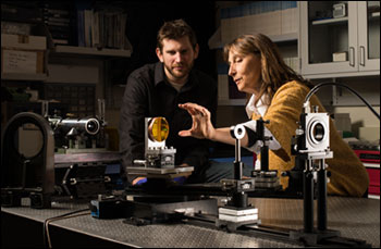 Kyle Fuerschbach, left, a graduate student at the University of Rochester's Institute of Optics, and Jannick Rolland, Brian J. Thompson Professor and director of the R.E. Hopkins Center, work on a freeform lens experiment in Goergen Hall.