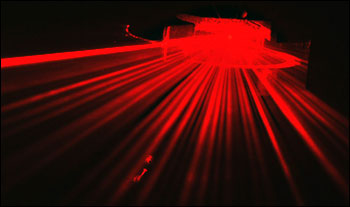 This image shows light scattering from a thin-fiber particle illuminated by a laser beam.