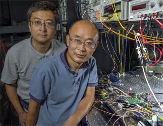 Guan Yang, front, and research associate Wei Lu pose in front of the laser communications breadboard they created to demonstrate high data-rate download and uplink speeds as well as precise distance and speed measurements.