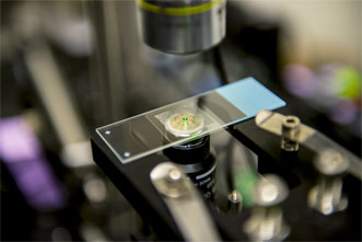 As they are cooled by a laser, nanocrystals emit a reddish-green glow that can be seen by the naked eye.