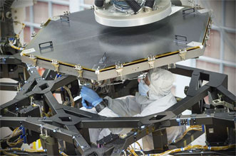 An engineer installs the first flight mirror onto the James Webb Space Telescope at NASA's Goddard Space Flight Center in Greenbelt, Md.