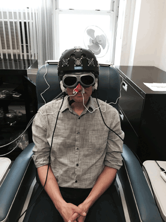 A staffer in Dr. Margaret Naeser's lab demonstrates the equipment built especially for the research: an LED helmet, intranasal diodes and LED cluster heads placed on the ears.