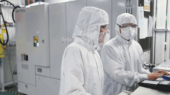 In semiconductor manufacturing, 193-nm wavelength deep-ultraviolet laser sources (white box behind engineers) help fabricate chips with feature sizes approaching 14 nm, which requires a tightly controlled source.