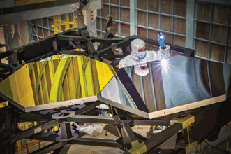 Larkin Carey, an optical engineer with Ball Aerospace, inspects primary mirror assemblies on JWST.