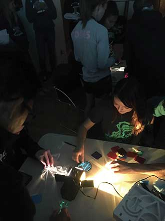 High School students play with light refraction at the first Café Scientifique meeting in Rio Rancho, N.M