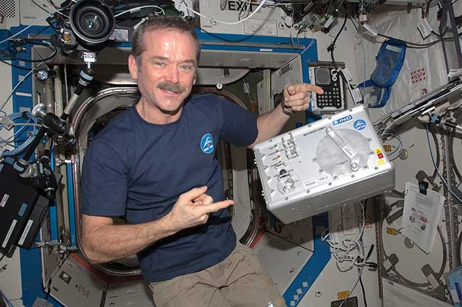Canadian Space Agency astronaut Chris Hadfield, floating in the International Space Station, together with INO's Microflow cytometer.