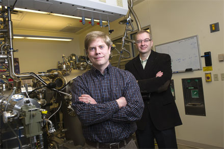 Purdue research engineer and graduate student Geoff Gardner (front) and professor Michael Manfra stand next to a molecular beam epitaxy system in the Manfra laboratories at Discovery Park.