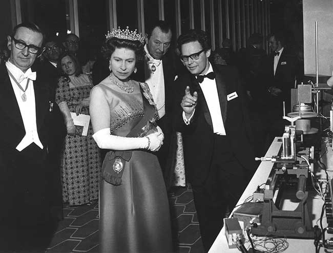 Murray Ramsay demonstrates video transmission over optical fibers to Queen Elizabeth II during a physics exhibition in London in 1971.