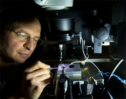 Sandia National Laboratories researcher Alec Talin inspects a plasmonic array sample using a probe station microscope.
