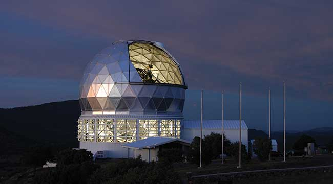 The mirror of the 9.2-meter Hobby-Eberly Telescope (HET) is visible through the open louvers in this twilight view.