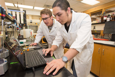 Research educator Tim Riedel works with a student in the University of Texas at Austin's Freshman Research Initiative on developing a diagnostic tool for malaria, Zika virus and more.