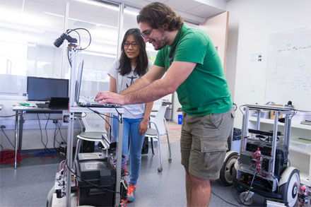 Dr. Timothy Riedel works with University of Texas at Austin undergraduate Jessica Popoola, a participant in the Freshman Research Initiative a discovery-research course that has been found to substantially improve students' likelihood of graduating, including with a STEM degree.