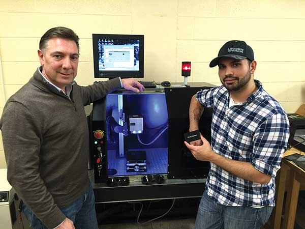 Nick Massa (left), a professor at Springfield Technical Community College, and his student Alex Rivera, stand in front of a 20-watt fiber laser marking and etching system built by Massa's students.