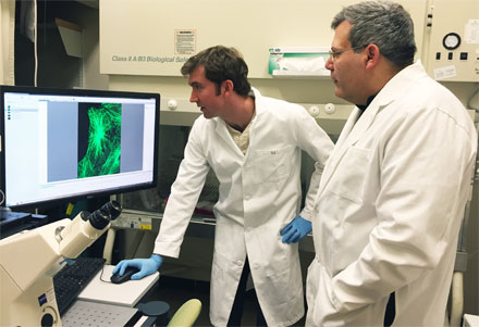Researchers Phil Santangelo and Eric Alonas are shown with a spinning disk confocal microscope used to image cells.