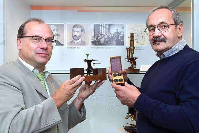 Dr. Wolfgang Wimmer, head of the Zeiss Archives (left) and Manfred Eichel display a simple microscope that dates back to 1850, likely built by Carl Zeiss himself.