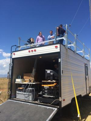 Principal investigator Greg Rieker, center, in blue, discusses the project with team members while atop their mobile laboratory in rural Colorado