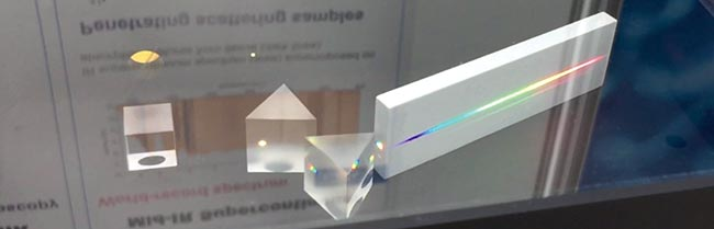 A supercontinuum laser entering a glass prism, which separates the wavelengths and produces a rainbow of colors.