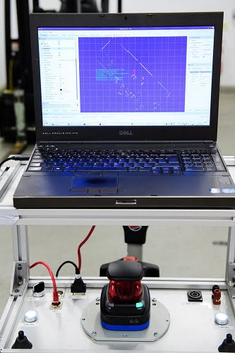 The laser technology which helps the forklifts operate autonomously is demonstrated on the screen, which is picking up nearby objects and translating it into a computerized diagram.