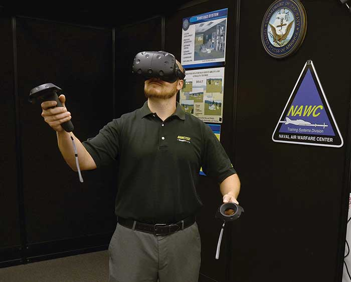 An engineer with the Naval Air Warfare Center Training Systems Division tests a commercial off-the-shelf (COTS) virtual reality headset.