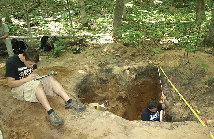 Two students mapping a pit profile to record how they were built and how they were filled in, capturing the life history of the cache pit.