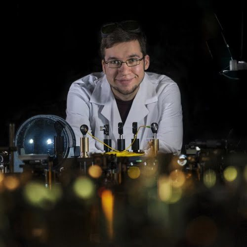Jan Szczepanek, a Ph.D. student from the Faculty of Physics of the University of Warsaw, with the innovative fiber laser.