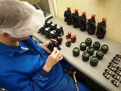 Assembly technician inspects components of Qioptiq thermal weapon sight components.