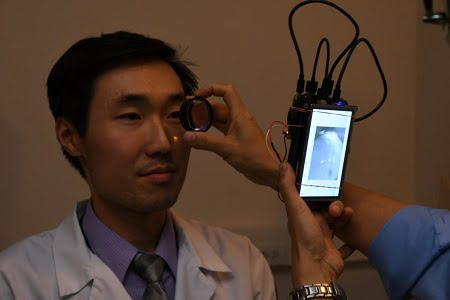 Dr. Bailey Shen, a resident in the department of ophthalmology and visual sciences in the UIC College of Medicine, has his retina photographed using a camera based in the Raspberry Pi 2 computer.