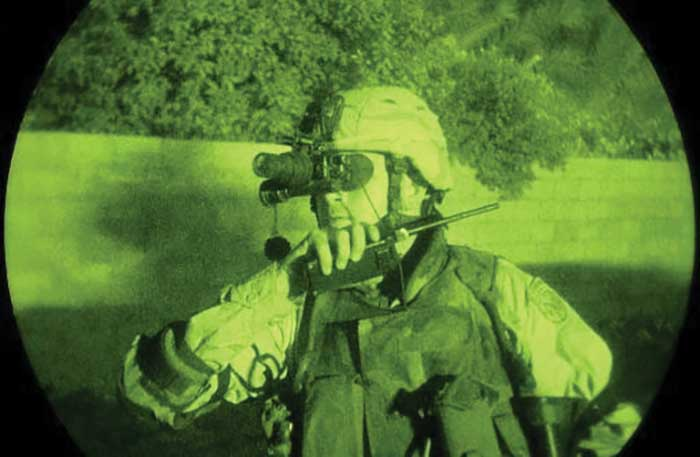 A close-up night-vision view of a U.S. Army soldier, 1st Battalion, 30th Infantry Regiment, wearing a Kevlar helmet with night-vision goggles attached.