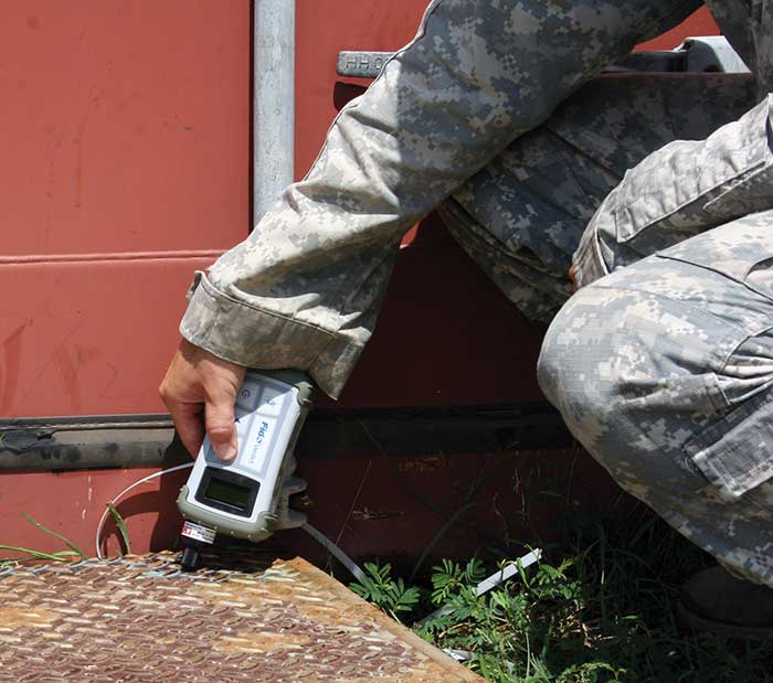 A National Guardsman samples a spill using a handheld device and Raman spectroscopy to identify the liquid.