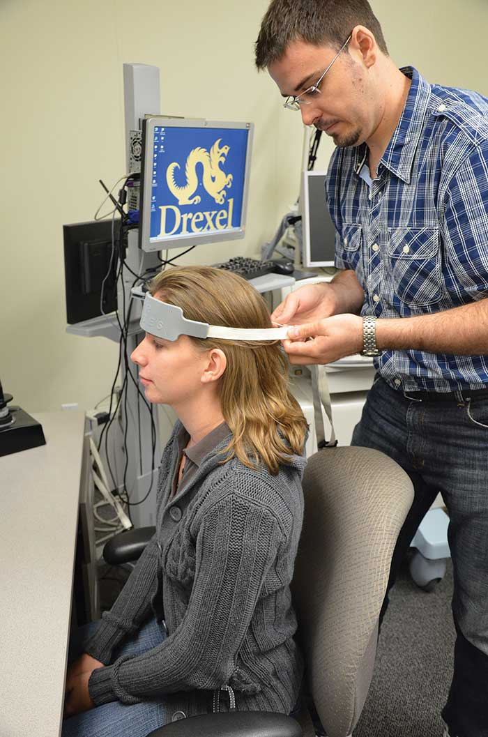 Hasan Ayaz placing a prefrontal fNIRS sensor band on a volunteer.