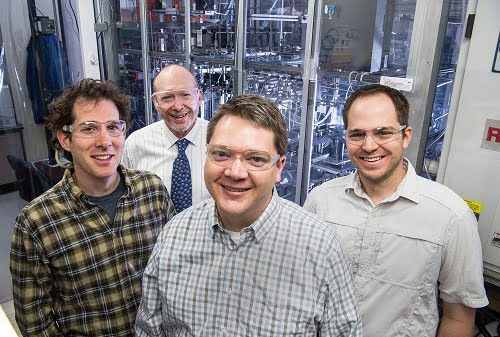 NREL researchers Myles Steiner (left), John Turner, Todd Deutsch and James Young stand in front of an atmospheric pressure MDCVD reactor used to grow crystalline semiconductor structures.