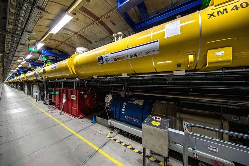 View into the 2.1-kilometer long accelerator tunnel of European XFEL with the yellow superconducting accelerator modules hanging from the ceiling.