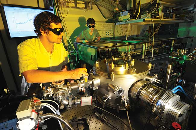 Doctoral students adjust a setup for the generation of attosecond light pulses