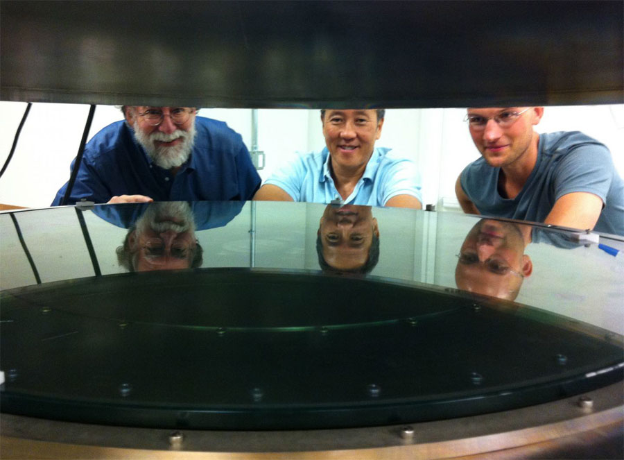 UC Santa Cruz researchers worked with Structured Materials Industries to design and build an atomic layer deposition (ALD) system large enough to accommodate telescope mirrors. Andrew Phillips, Nobuhiko Kobayashi, and David Fryauf (l to r) examine the deposition chamber.
