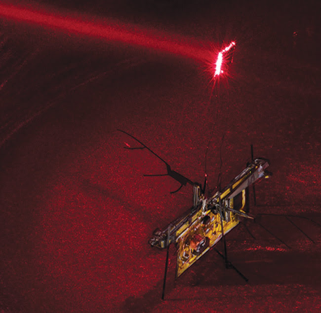 To power RoboFly, the engineers point an invisible laser beam (shown here in red laser) at a photovoltaic (PV) cell attached above the robot. The cell converts the laser light into electricity. Courtesy of Mark Stone/University of Washington