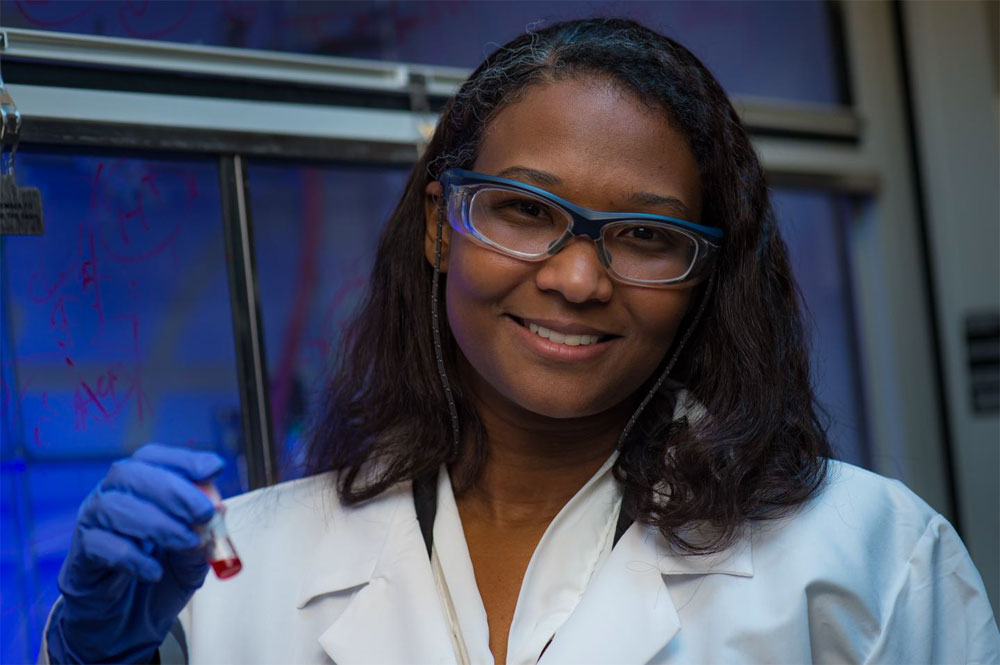 Rice University's Eilaf Egap, an assistant professor of materials science and nanoengineering and chemical and biomolecular engineering, holds a vial of quantum dots her lab is using to catalyze the creation of functional polymers. Courtesy of Jeff Fitlow/Rice University.