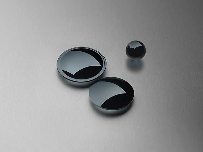 Precision-molded IR lenses and a ball preform made from chalcogenide glass.