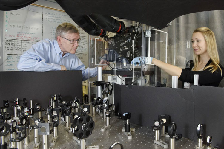 Professor W. E. Moerner, left, and postdoctoral scholar Anna-Karin Gustavsson position a sample on the new TILT3D microscope. Stanford University.