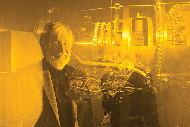 Günther Dausmann with his jet engine hologram in a wall inset with the yellow laser illuminating from behind the transmission hologram.