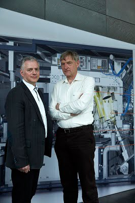 Vadim Banine (left), Director of Research of ASML, and systems engineer Erik Loopstra, in front of a model of a ASML EUV lithography system. Courtesy of Zeiss.