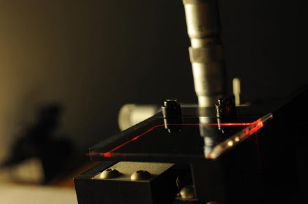 Researchers used an inkjet printing method to create the waveguide shown here. Sending laser light through the waveguide (red) allowed them to measure the waveguide's optical properties. Courtesy of Fabian Lütolf, CSEM.